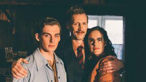 Veli (Lauri Tilkanen), Touko (Pekka Strang) och Kaija (Jessica Grabowsky) står alla bredvid varandra och ser rakt in i kameran.