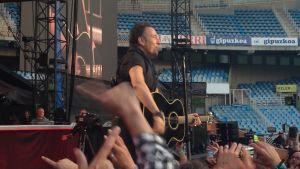 Bruce Springsteen laulaa ja soittaa lavalla