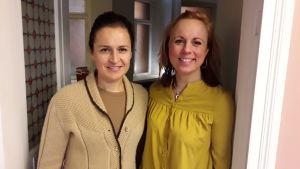 Anne Teir-Siltanen och Anna Bertills står bredvid varandra i senapsgula kläder i en dörröppning.