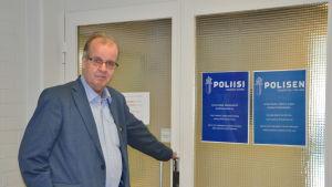 Jan Storing står vid ingången till poliskontoret och håller i dörrhandtaget.