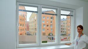 Utsikt genom fönster mot ett modernt kvarter.