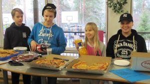 neljä kahdeksasluokkalaista myyvät leivonnaisia luokkarahaston hyväksi koulun aulassa