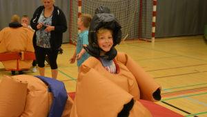 Flicka utklädd i sumobrottarkläder