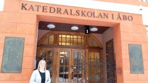 Rektor Marianne Pärnänen står vid ingången till Katedralskolan i Åbo