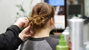 En frisör lagar en uppsättning med flätor åt en ung kvinna.