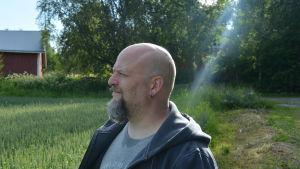 Mansperson i profil utomhus. Solen lyser, gräset är grönt.