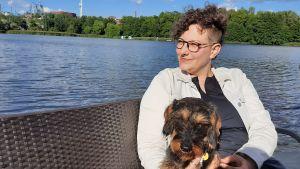 Pia Rickman sitter vid vattnet med en tax i famnen.