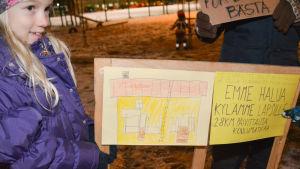 Flicka håller i skylt med bild på skola