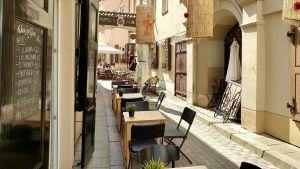 Restaurang i Vilnius, Litauen väntar på kunder till sin uteservering.