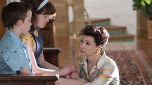 Judy Garland (Renée Zellweger) sitter på knä framför sina två små barn, de ser alla ledsna ut.
