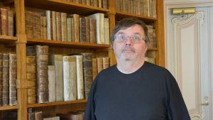 Professor Antti Laato framför en bokhylla i Teologicum.