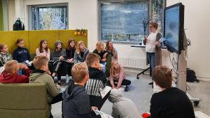 Elever lyssnar på en lärare. De sitter på en soffa och på golvet.
