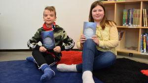 Aron Aaltonen och Wilma Kostiainen håller upp var sin bok, de sitter på golvet.