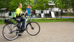 Mirjam Manninen står med sin elcykel utanför Muminparken.