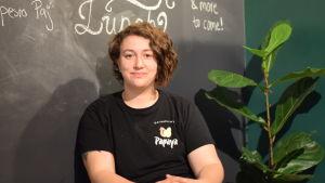 En kvinna sitter. I bakgrunden en svart tavelvägg. Skrivet med vit krita dagens lunch.