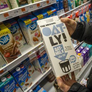 En person håller i en kartong med havremjölk av märket Oatly i den butik.