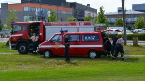 Två brandbilar och brandmän, en med håv och två med bur.