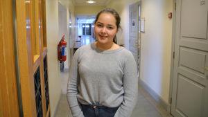 Frida Granroth ler till kameran i en korridor i Borgå gymnaisum