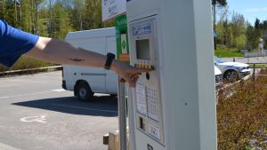 En hand som trycker på knapp i parkeringsautomat.