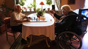 En äldre man sitter och spelar spel med en äldre kvinna som sitter i rullstol.