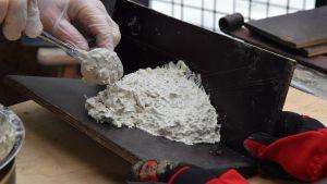 En hand med engångshandske håller i en sked och formar en igloo-formad form av betong på en vinkel av vattenfast faner för att använda till en svalholk av träbetong.