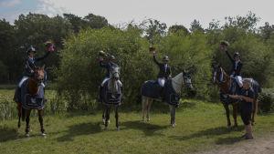 Fyra hästar med ryttare står på rad.