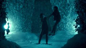 Rose the Hat (Rebecca Ferguson) står i en vintrig busklabyrint och slänger Alba (Kyliegh Curran) upp i luften.