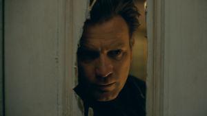 Närbild på Danny (Ewan McGregor) då han tittar in genom ett hål som hackats upp med yxa i en dörr.