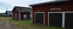 Flera rödmyllade hus på rad,. Ovanför garaget finns en skylt där det står Rosasgården.
