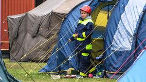 Pojke i brandkårsdräkt framför ett tält.