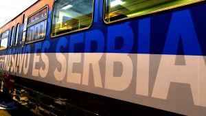 Kosovo är Serbien skrivet på en tågvagn på spanska, på en bakgrund i den serbiska flaggans färger.