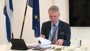 Pekka Haavisto bläddrar i sina anteckningar inför en presskonferens i Bryssel måndagen den 22 mars.