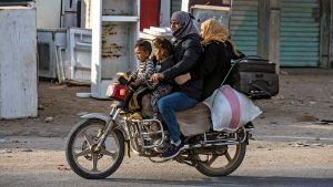 Vad som ser ut som en familj på en motorcykel kör i ett bostadsområde.
