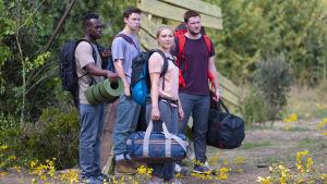 Josh (Jackson Harper), Mark (Will Poulter), Dani (Florence Pugh) och Christian (Jack Reynor) står med sina kassar vid ingången till kollektivet i Hårga.