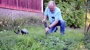 En man gräver i marken med en spade. I gräset ligger en metalldetektor.