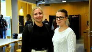 två unga kvinnor står i asa-aulan