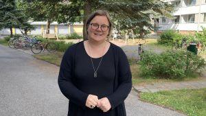 Mia Henriksson, en kvinna i svart tunika, står på sin innergård.