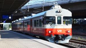 A-tåget anländer till Ilmala station en solig dag.