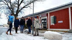 En grupp människor står utanför en röd byggnad som är Ekenäs naturum.