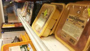 Broilerförpackningar med rabattlappar i en kyldisk. Också andra köttrprodukter med rabattlappar syns.