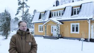 niklas tevajärvi framför sitt hus, en gul villa.