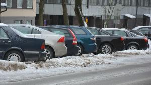 Flera bilar står parkerade i rad vintertid.