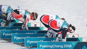 Heidi Weng och Ingvild Flugstad Östberg i skidbyte under skiathlontävlingen.