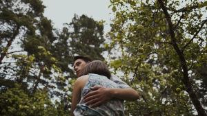 Elvis (Johannes Brotherus) står i en äppelträdgård och håller om Onerva (Mimosa Willamo).