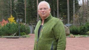 En äldre man med rakat grått hår och grön jacka står ute på en gård. Lite skog i bakgrunden.