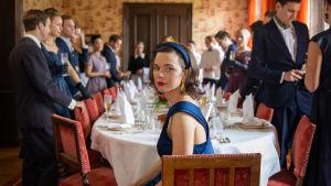 Nina sitter på ändan i ett bord och ser ensam och ledsen ut, trots att bordet är omgivet av massor av gäster.
