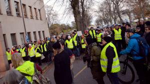 En stor grupp människor i gula reflexvästar står och demonstrerar framför en byggnad.