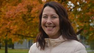Ann-Sofi Backgren ler mot kameran med höstlöv i bakgrunden.
