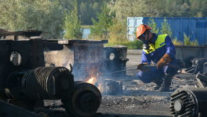 Man med ansiktsmask och skyddhjälm som bränner sönder metall med ett svetsliknande verktyg.