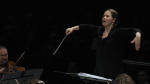Emilia Hoving står framför en orkester och dirigerar med armarna nästan lyfta.